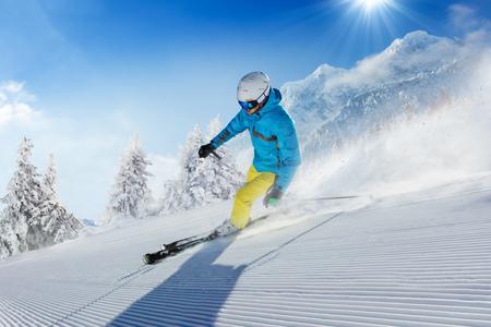 알파인 산에서 경사면을 실행하는 젊은 남자 스키어. 겨울 스포츠 및 레크리에이션, 레저 야외 활동.