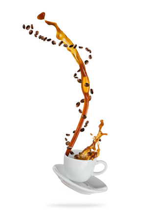 Splashing coffee drink from the cup with flying beans, isolated on white background Foto de archivo