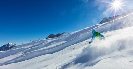 젊은 남자 스키어 가루 눈, 알파인 산에서에서 내리막을 실행합니다. 겨울 스포츠 및 레크리에이션, 레저 야외 활동.