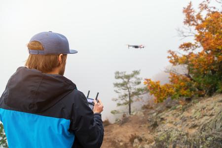 Hombre joven que maneja el abejón, usando teledirigido. Nueva tecnología y tendencias en la grabación de fotos y videos. Foto de archivo - 88606276