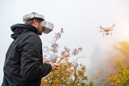 Hombre joven que maneja el abejón, usando gafas de realidad virtual. Nueva tecnología y tendencias en la grabación de fotos y videos. Foto de archivo - 88606278