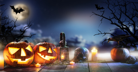 Spooky halloween pumpkins on wooden planks with dark horror background. Celebration theme, copyspace for text. Stock Photo