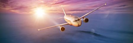 Avión comercial que vuela sobre las nubes en luz dramática de la puesta del sol. Alta resolución de la imagen. Concepto de viaje rápido y transporte Foto de archivo