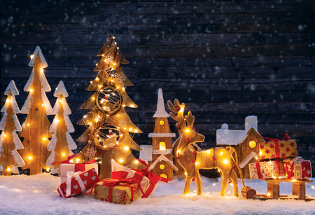 Christmas backgound with illuminated wooden village, moose and christmas tree. Dark wooden background with free space for text. Celebration of christmas