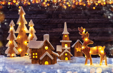 Christmas background with illuminated wooden village, moose and trees. Dark wooden background with free space for text. Celebration of christmas