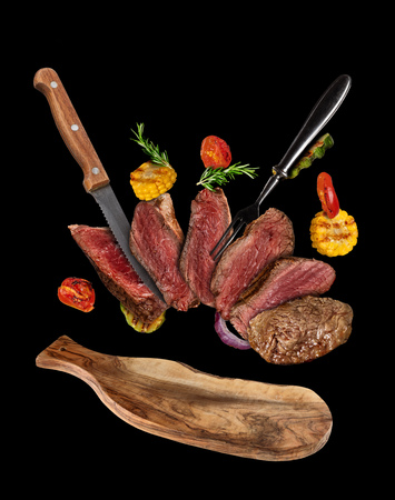 Flying beef steaks with grilled vegetable served on plate. Concept of flying food. Separated on black background. High resolution size Stok Fotoğraf - 89584968