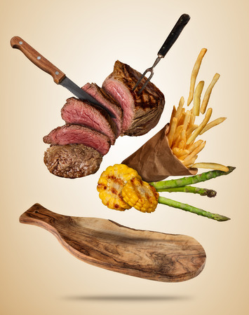 Flying beef steaks with grilled vegetable and french fries served on wooden cutting board. Concept of flying food. Separated on soft colored background. High resolution size Stock Photo