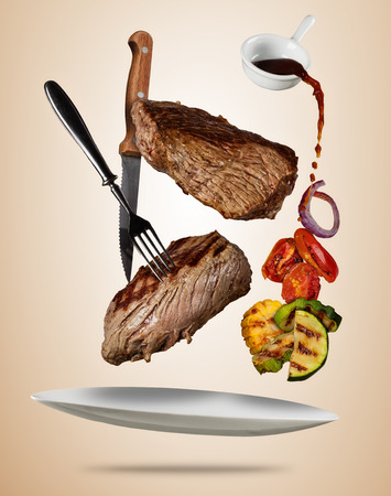 Flying beef steaks with grilled vegetable served on plate. Concept of flying food. Separated on soft colored background. High resolution size Stok Fotoğraf - 90021849
