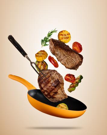 Flying beef steaks with grilled vegetable on pan. Concept of flying food. Separated on soft colored background. High resolution size Stok Fotoğraf - 89584967