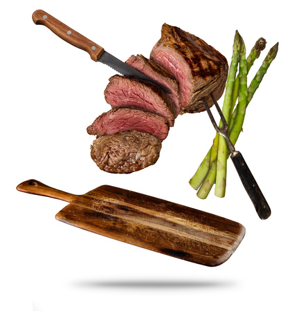 Flying beef steaks with grilled asparagus served on wooden cutting board. Concept of flying food. Separated on white background. High resolution size