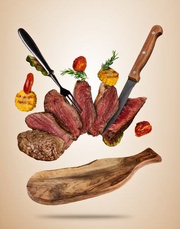 Flying beef steaks with grilled vegetable served on wooden cutting board. Concept of flying food. Separated on soft colored background. High resolution size Stok Fotoğraf