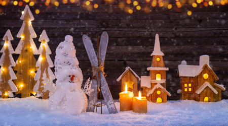 Christmas background with illuminated wooden village, snowman and christmas tree. Dark wooden background with free space for text. Celebration of christmas