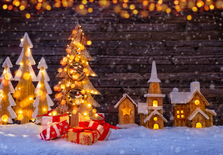 Christmas background with illuminated wooden village and christmas tree. Dark wooden background with free space for text. Celebration of christmas