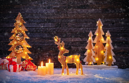 Christmas backgound with illuminated moose and christmas tree. Dark wooden background with free space for text. Celebration of christmas