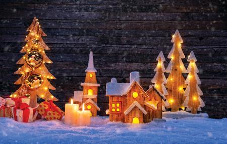 照らされた木製の村およびクリスマスツリーが付いているクリスマスの背景。テキスト用の空き領域を持つ暗い木製の背景。クリスマスのお祝い