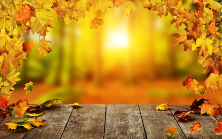 Autumn background with falling leaves and empty wooden table, ideal for product placement or free space for text. Seasonal abstract vivid colored background