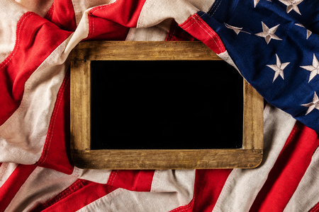 Close-up of USA flag in grunge design with woden blackboard for copyspace. Motive of celebration Stock Photo