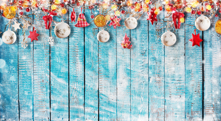 Christmas background with hand made cloth decorations on wooden planks. Free space for text. Celebration and decorative design.