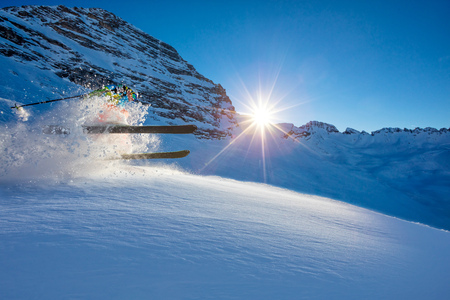 Freerider skier jumping in fresh powder snow in beautiful Alpine landscape. Fresh powder snow, blue sky on background.