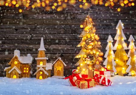 Illuminated wooden village and Christmas tree. Dark wooden background with free space for text.