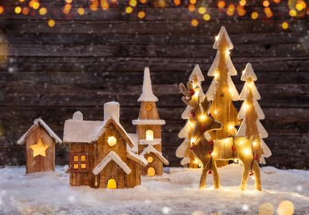 照らされた木製の村、ムースと木々とクリスマスの背景。暗い木製の背景とテキスト用の空き領域。クリスマスのお祝い