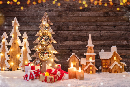 Holidays background with illuminated Christmas tree, gifts and wooden village. Dark wooden background with free space for text. Celebration of christmas