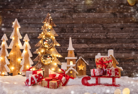 Holidays background with illuminated Christmas tree, sledge with gifts and wooden village. Dark wooden background with free space for text. Celebration of christmas Stock fotó