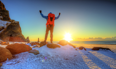 Young man traveler with backpack, celebrating with gesture, Iceland. Concept of freedom and travel. Winter landscape, outdoor activity and sport