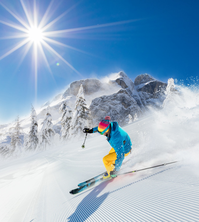 Skier on piste running downhill in beautiful Alpine landscape. Blue sky on background. Free space for text 스톡 콘텐츠