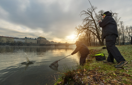Two sport fishermen trying to catch fish in river, urban fishing. Leisure and hobbies activities in outdoor