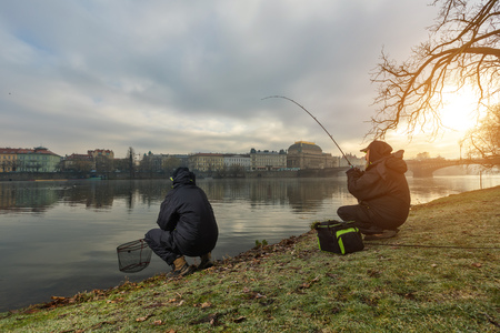Two sport fishermen catching fish from river, urban fishing. Leisure and hobbies activities in outdoor