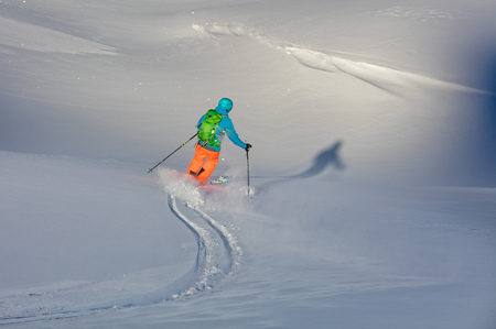 Young freeride skier running downhill in fresh powder snow. Winter sports and outdoor activities Stock Photo