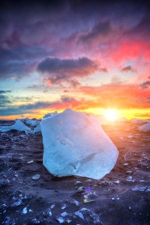 アイスランドの有名なダイヤモンドビーチの上に美しい夕日。この砂の溶岩ビーチは、氷河ラグーンジョクルサルロンの近くに配置された多くの巨 写真素材