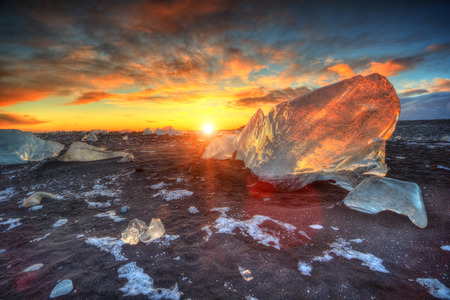Beautiful sunset over famous Diamond beach, Iceland. This sand lava beach is full of many giant ice gems, placed near glacier lagoon Jokulsarlon. Stock Photo
