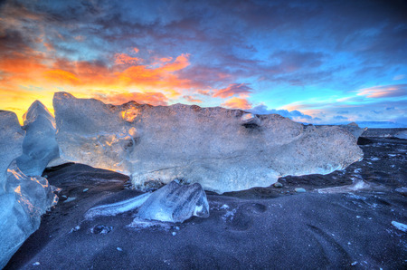 Beautiful sunset over famous Diamond beach, Iceland. This sand lava beach is full of many giant ice gems, placed near glacier lagoon Jokulsarlon. 스톡 콘텐츠