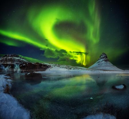 美しいオーロラボレアリスと凍った水を持つカークジュフェル山は、冬、アイスランドに落ちます。アイスランドの有名な自然遺産の一つ。