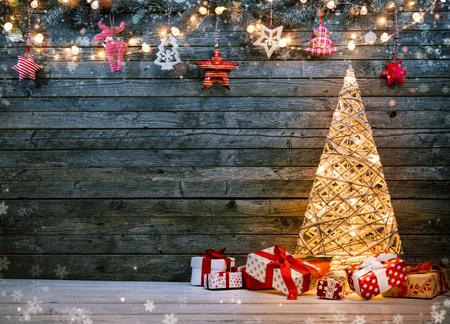 イルミネーション クリスマス ツリー、プレゼント、デコレーションと休日の背景。暗いテキストの空き領域と背景の木。クリスマスのお祝い
