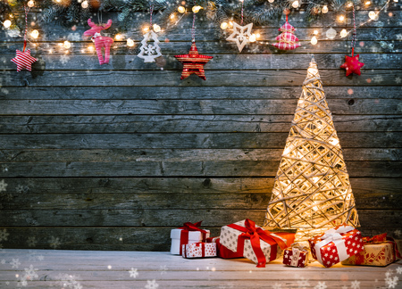 Holidays background with illuminated Christmas tree, gifts and decoration. Dark wooden background with free space for text. Celebration of christmas Stockfoto