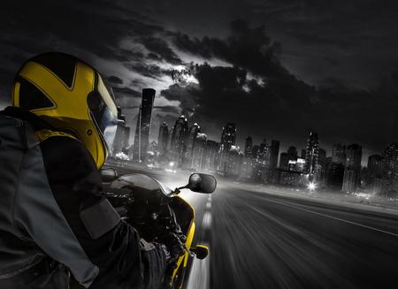 現代の都市に向かうスーパースポーツバイクライダーの詳細。スピード、旅行、自由の概念。背景にドバイの超高層ビル