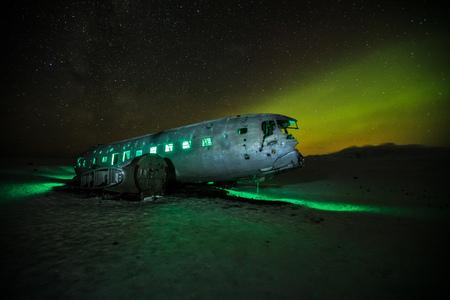 Beautiful illuminated airplane wreck on Solheimasandur, Iceland. Famous tourist place of abandoned wreck of American navy, Dakota.  Stock Photo