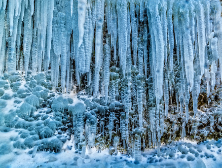 Detail of massive group of icicles on rock. Beautiful frozen water faling from rocky peak, Iceland