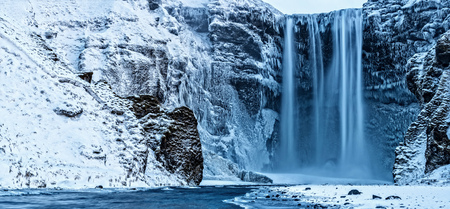 Beautiful panoramic photo of Skogafoss waterfall in winter, Iceland. Long exposure