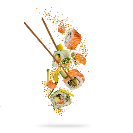 Flying pieces of sushi with wooden chopsticks, separated on white background. Flying food and motion concept. Very high resolution image