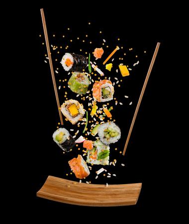 Partes de voo de sushi com chopsticks e a placa de madeira, isolados no fundo preto. Voando comida e conceito de movimento. Imagem de alta resolução Foto de archivo