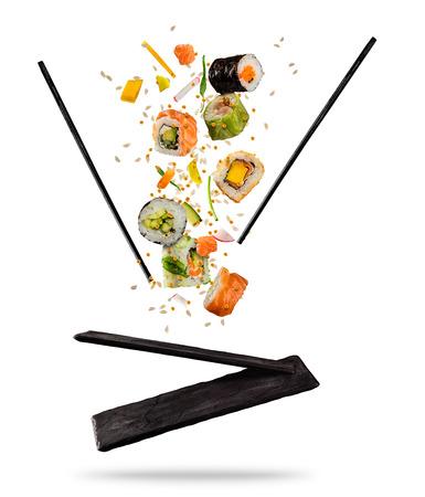 Fliegende Stücke Sushi mit den hölzernen Essstäbchen und Steinplatte, lokalisiert auf weißem Hintergrund. Flying Food und Motion-Konzept. Sehr hochauflösendes Bild