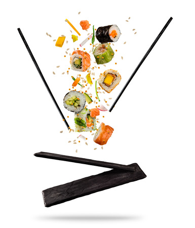Flying pieces of sushi with wooden chopsticks and stone plate, isolated on white background. Flying food and motion concept. Very high resolution image