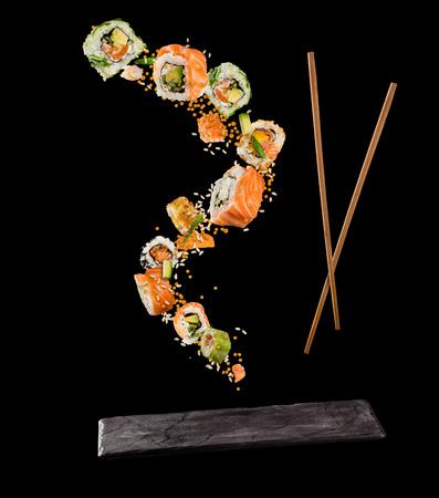Vliegende stukjes sushi met houten stokjes en stenen plaat, geïsoleerd op zwarte achtergrond. Vliegend voedsel en motieconcept. Zeer hoge resolutie afbeelding Stockfoto