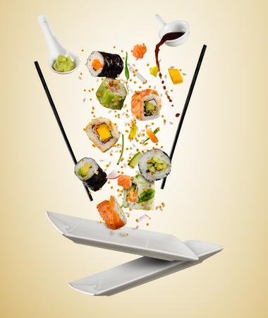 Fliegende Stücke Sushi mit den hölzernen Essstäbchen, getrennt auf beige Hintergrund. Flying Food und Motion-Konzept. Sehr hochauflösendes Bild