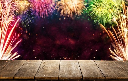 Celebration background with fireworks explosions and empty wooden planks, ideal for product placement Stock Photo