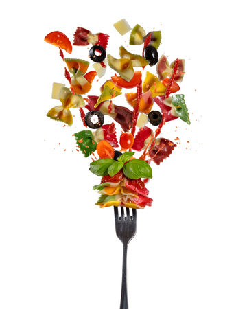 Concept of flying food with fork and traditional italian farfalle pasta with vegetable. Isolated on white background. Very high resolution image Stock Photo